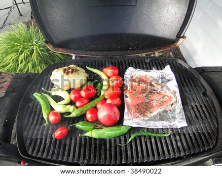 Pacific Northwest barbecue - salmon on foil, tomatoes, squash and peppers on a grill - stock photo