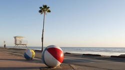 Pacific ocean beach, Oceanside California USA. Ball, lifeguard tower, life guard watchtower hut and tropical palm tree, sky, beachfront street, waterfront road. Los Angeles vibes, aesthetic atmosphere