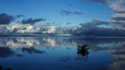 Pacification of nature. The sky and clouds are reflected in the smooth surface of the water. The boat is afloat.