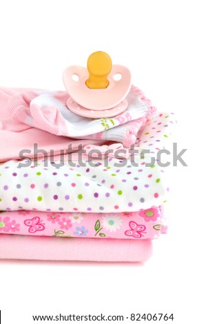 Pacifier and a pile of pink baby clothes, isolated on white