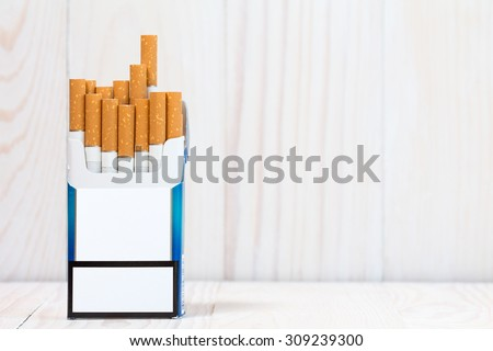 Pack of cigarettes on white wood  background. With copy-space for text
