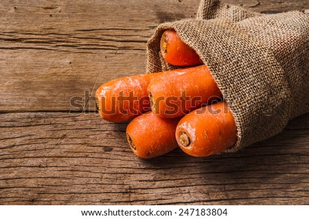Pack of Fresh Harvest Carrot with Vintage Burlap Bag on Wood Table Background, Concept and Idea of Food Cook Rustic Still life Style.