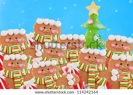 Pack of gingerbread men cookies in a winter wonderland wearing a scarf, while snowing with christmas tree in the background