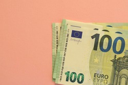 Pack of one hundred euro banknotes with orange background