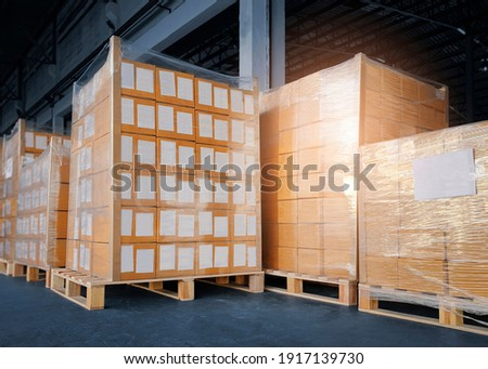 Package boxes. Interior of storage warehouse with stack of card board boxes wrapped plastic on pallet rack. L-shape pallet corrugated paper cardboard Angle corner edge protector.  Stock fotó ©