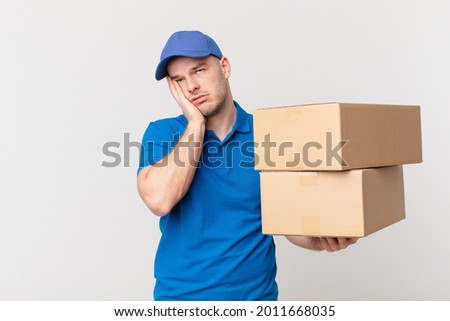 package deliver man feeling bored, frustrated and sleepy after a tiresome, dull and tedious task, holding face with hand Сток-фото ©