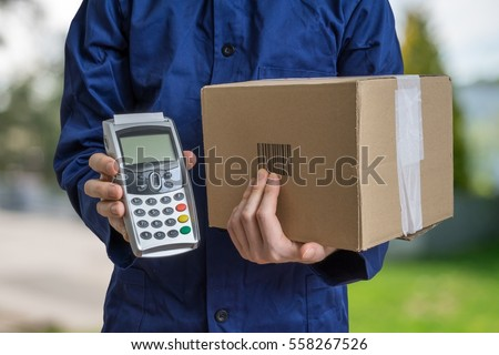 Package delivery concept. Man holds cardboard box and payment terminal in hands. #558267526