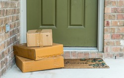 Package delivery on doorstep. Boxes and postal delivery on modern brick home doorstep on front porch