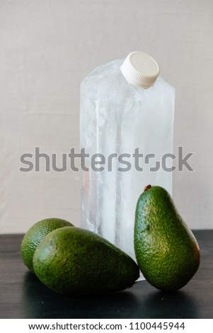 Package design mock-up from ice with plastic cap and three avocados on neutral background. Innovative food concept and humorist story.  #1100445944
