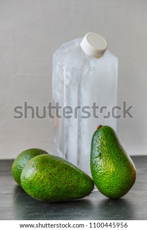 Package design mock-up from ice with plastic cap and three avocados on neutral background. Innovative food concept and humorist story.  #1100445956