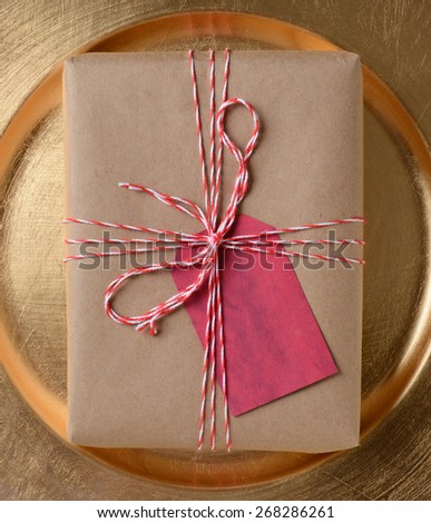 Package on a gold platter, The gift is wrapped in plain brown paper and tied with red and white twine. A blank red gift tag is attached to the present.
