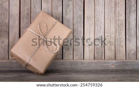 Package wrapped in brown paper and string leaning against a wood fence