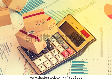 Packaging boxes and calculator on technical chart of financial expansion. Idea of marketing planning and shipping costs, freight forwarding business concept.Control financial budget and service charge Stock foto ©