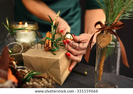Packaging holiday gifts.Woman packs a Christmas gift and decorating the house with Christmas decorations