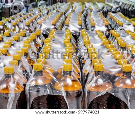 Packaging plastic bottles at the brewery. Packed shrink packaging film.