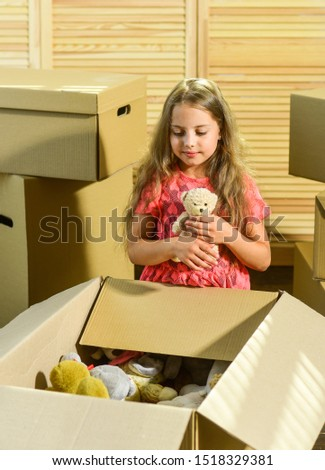Packaging things. Move out concept. Stressful situation. Divorce and separation. Family problem. Prepare for moving. Moving out. Moving routine. Only true friend. Girl child play with toy near boxes. #1518329381