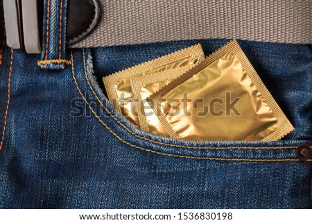 packaging with condoms in the pocket of jeans, the concept of protection against sexually transmitted diseases, unwanted pregnancy, sexual education in educational institutions #1536830198