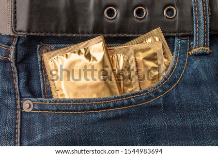 packaging with condoms in the pocket of jeans, the concept of protection against sexually transmitted diseases, unwanted pregnancy, sexual education in educational institutions #1544983694