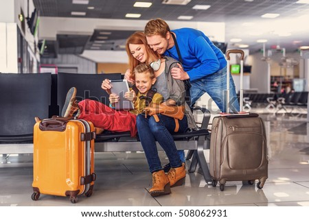 Packed and prepared for take-off. Smiling happy family doing holiday trip and looking map on digital tablet at airport hall