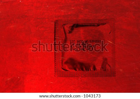 packed condom over a red background