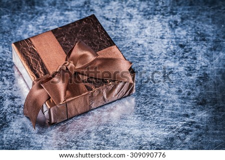 Packed present with tied bow on metallic background holiday concept.