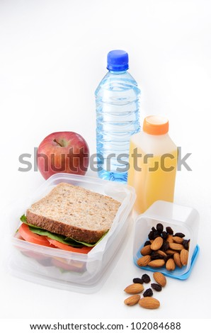 Packed sandwich, apple, orange juice, dried fruit and nuts with a bottle of water isolated on white