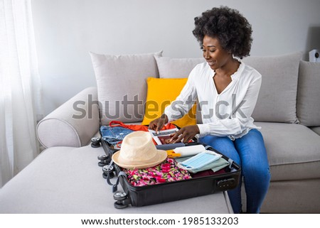 Packed suitcase for business travel after COVID-19. Suitcase packing for travel, COVID-19. Woman packing suitcase for summer vacation trip, including face masks and travel-sized antibacterial hand gel Stockfoto ©