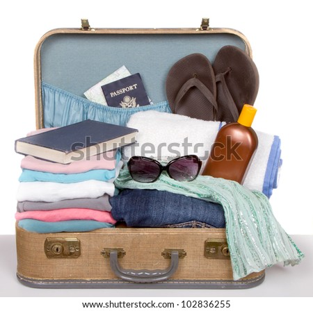 Packed vintage suitcase full of vacation items