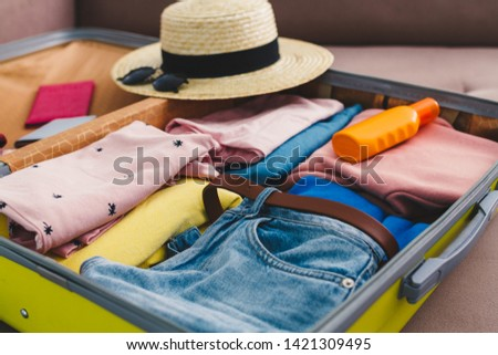 Packing a luggage at home for a new journey and travel. Vacation travel suitcase #1421309495