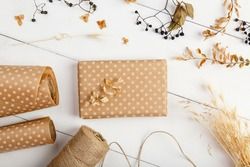 Packing autumn present in decorarive paper cover for delivery, shipping service. Craft present gift box on autumn background. Autumn birthday present. Fall leaves decor. Celebration thanksgiving day