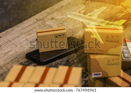 Packing boxes small goods and cell phone with a plane flies above world map. business concept about transportation, global shipping, international freight, overseas trade, regional, services remotely.