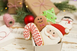 Packing christmas cookies in a box, christmas gift concept. Christmas cookies in a box with gifts, lights and fir branches on white vintage wooden table