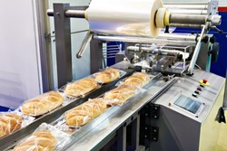 Packing machine with a roll of film for loaves of bread