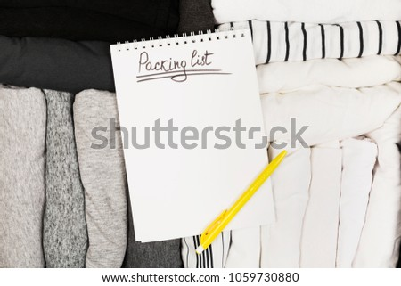 Packing of monochrome clothes in black suitcase. Packing list in white notebook. Top view, copy space