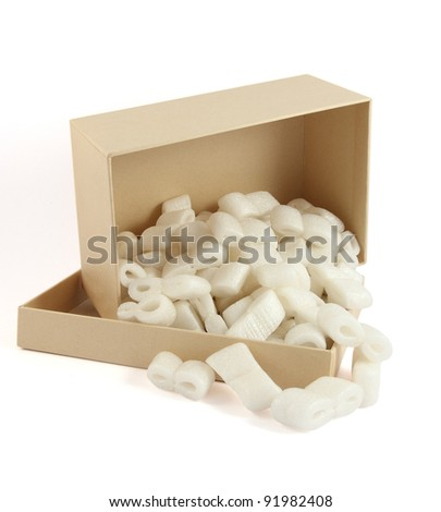 Packing peanuts spilling from open cardboard box - stock photo