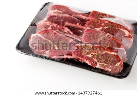Packing raw Raw lamb chops on white background