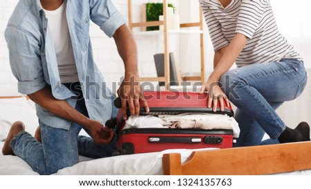 Packing suitcase. Couple trying to close valise, preparing for honeymoon