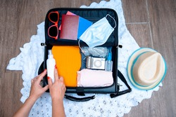 Packing suitcase luggage with face mask and sanitizer with clothes for new normal travelling during Coronavirus pandemic. Cut out image of female hands preparing for the vacation travel. Top view flat