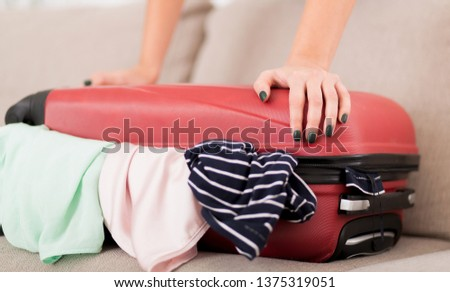 Packing valise. Woman trying to close full suitcase, closeup
