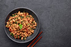 Pad Krapow Gai - Thai Basil Chicken in black bowl at dark slate background. Pad Krapow is Thai cuisine dish with minced chicken or pork meat, basil, soy and oyster sauces. Thai Food. Copy Space
