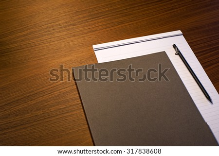 Pad of paper, file & pencil on wooden business desk