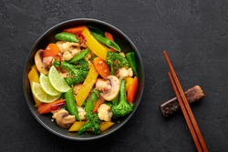 Pad Pak Ruam or Veg Thai Stir-Fried Vegetables in black bowl on dark slate backdrop. Pad Pak is thailand cuisine vegetarian dish with mix of vegetables and sauces. Thai Food. Top view