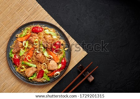 Pad Woon Sen or Thai Pork Glass Noodle Stir-Fry in black plate on dark slate backdrop. Pad Woon Sen is a Thai cuisine dish of glass bean noodles, meat, tomatoes, carrots, egg, sauces. Thai Food. Zdjęcia stock ©