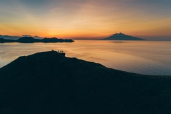 Padar island.Wild Indonesia. Flores. tropical paradise. Labuan Bajo. drone shooting. Wild beaches, aerial view. boat trip safari. a group of people watching the sunset on the hill. Vulcano view