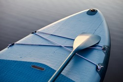 Paddle board and surf board with paddle on blue water surface background close up. Surfing and SUP boarding equipment in sunset lights close-up. Outdoor water sports. Surfing lifestyle backgrounds.