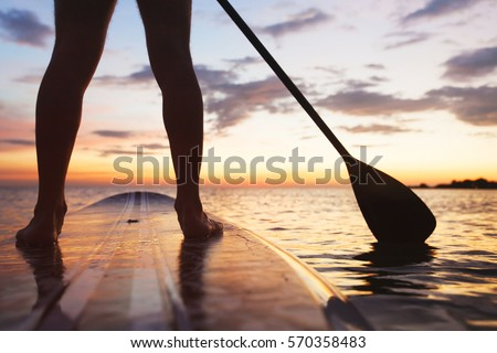 paddle board on the beach, close up of standing legs and paddle - Shutterstock ID 570358483