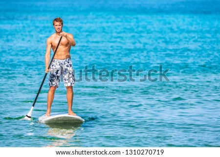 Paddle board stand up sup paddleboard man athlete paddling through blue ocean water background watersport activty on Hawaii beach. Active healthy lifestyle. #1310270719