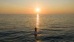 Paddle boarder. Black sunset silhouette of young man on stand up paddleboard. Water sport activity, SUP surfing. silhouette at sunset, recreation sport paddling ocean beach surf orange. Sochi