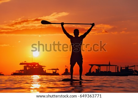 Paddle boarder. Black sunset silhouette of young sportsman on stand up paddleboard. Water sport activity, SUP surfing in adventure camp on active family summer beach vacation.