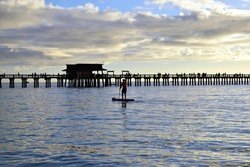 Paddle Boarder by Naples Pier at Dusk